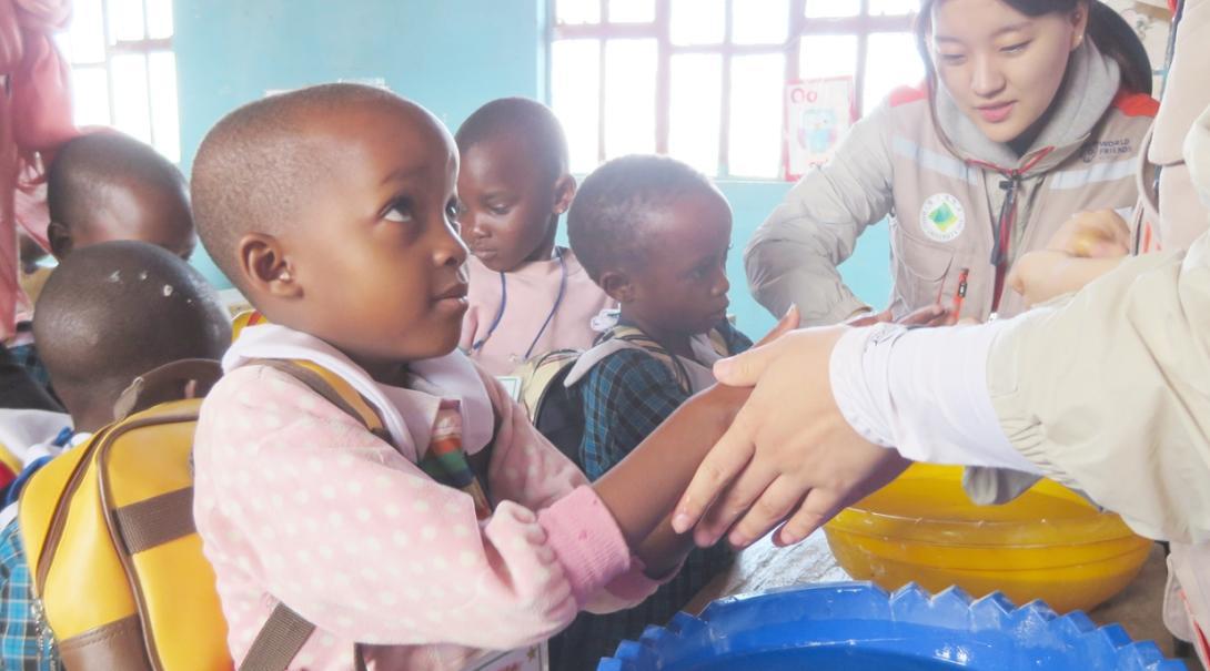 タンザニアの子供たちへの手洗い指導にあたる高校生ボランティア